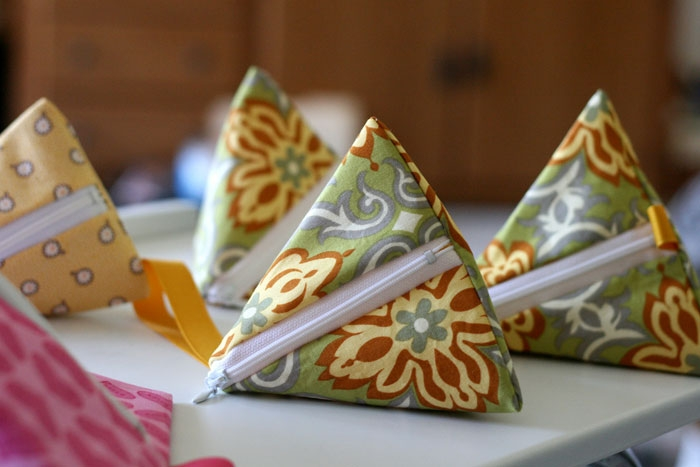 Table full of teeny triangle bags.